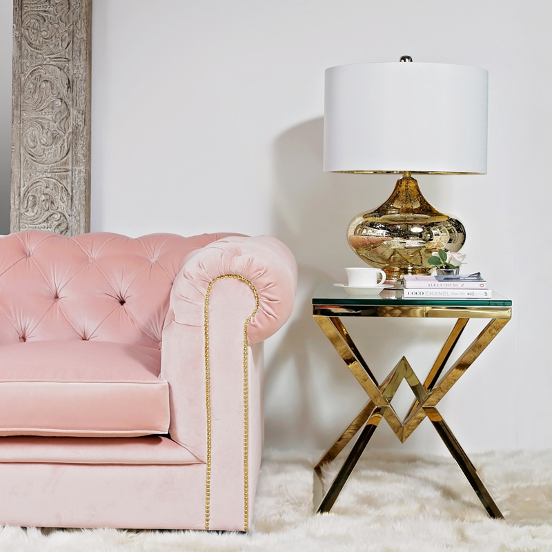 A PINK VELVET ARM CHAIR AND GOLD SIDE TABLE