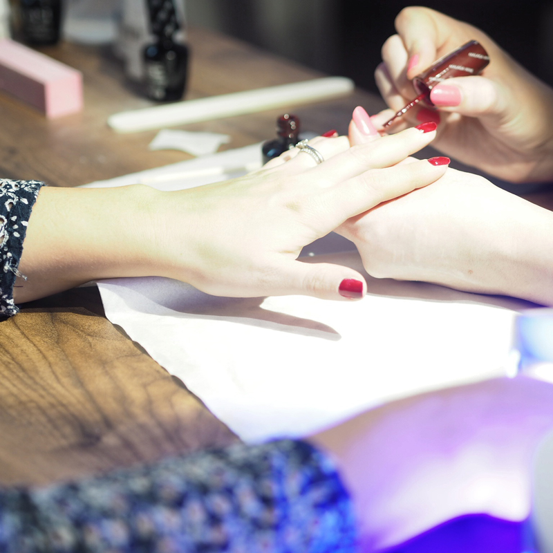 Woman getting a manicure with oxblood red gel nail polish at Q61 Studio Leeds