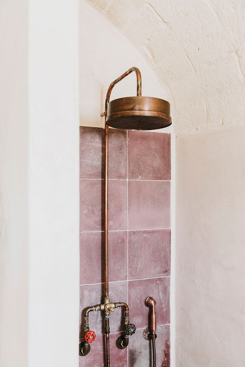 Pink tiled bathroom with copper fixtures