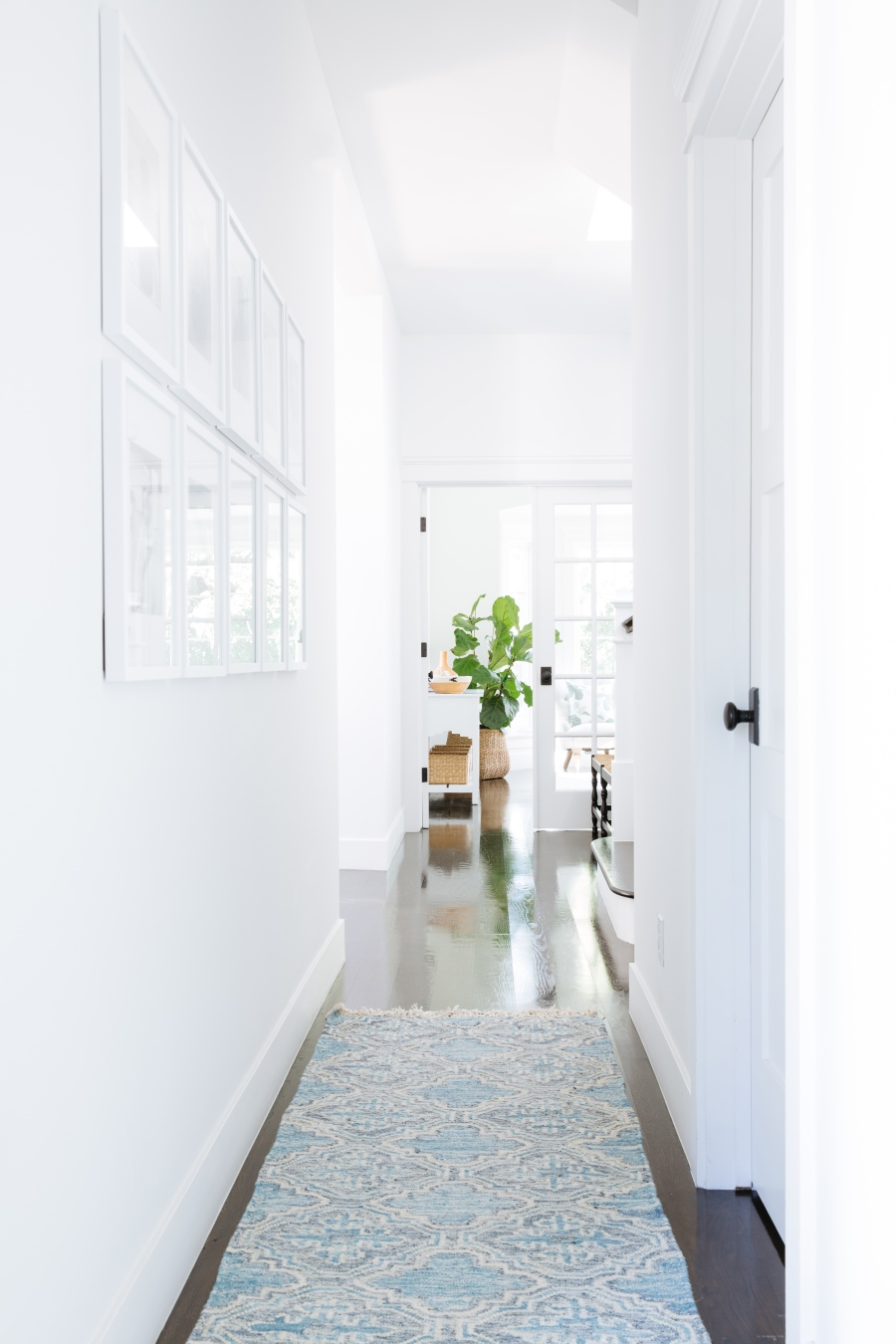 White hallway with blue and white rug