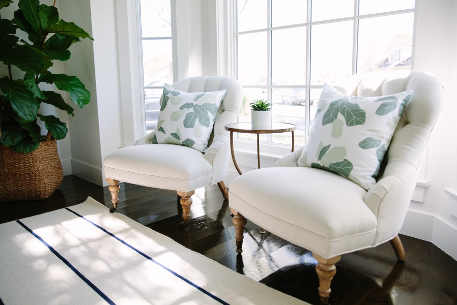 Cream chesterfield chairs with palm leaf print cushions
