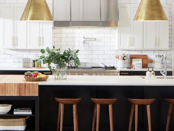 kitchen with black island and gold pendant lights