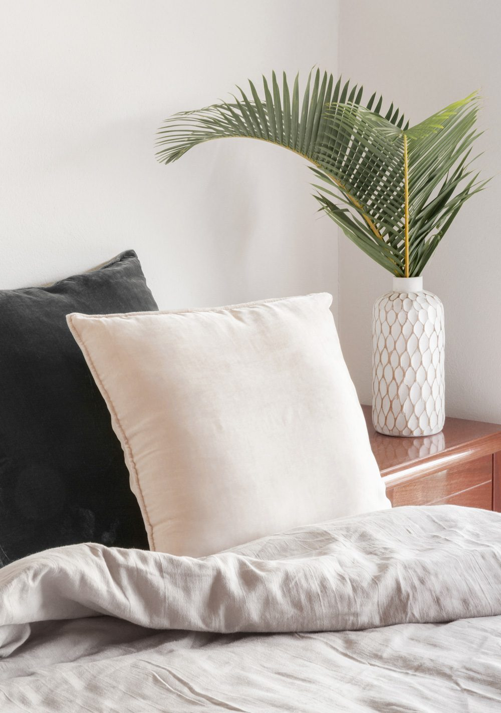 Cozy bed with palm leaf plant on side table in a white vase